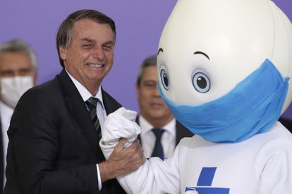 Bolsonaro segura o braço de Zé Gotinha em dezembro após mascote se negar a cumprimentá-lo com aperto de mão.