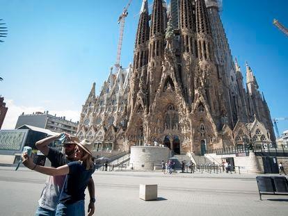 Casal tira  foto diante da Sagrada Familia, em Barcelona.
