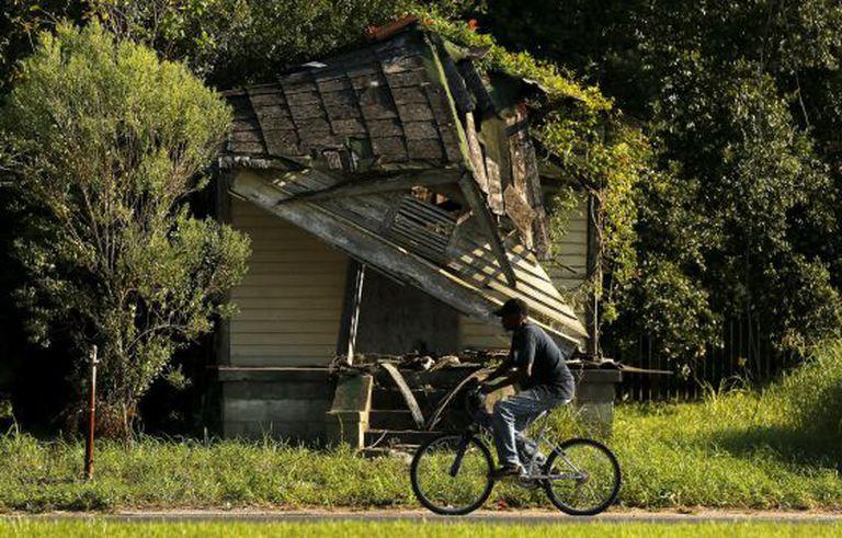 Homem passa diante de casa abandonada no Distrito 9 de Nova Orleans.