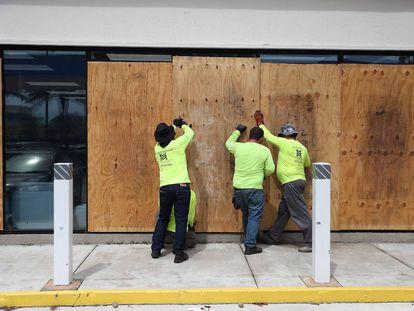 Trabalhadores de Miami cobrem as fachadas dos edifícios ante a possível chegada do furacão Dorian.