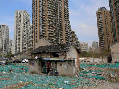 Em um canto de Xangai, rodeado por um muro de concreto, se encontra um dos terrenos mais valiosos do mundo entre escombros e lixo. O bairro de Guangfuli é o sonho de um investidor imobiliário: um lote em meio a um dos mercados imobiliários mais caros e de rápido crescimento do planeta. Mas a realidade é mais parecida com um pesadelo, já que centenas de pessoas que vivem ali se negaram a abandonar suas casas deterioradas durante quase 16 anos. Na imagem, Tao Weiren se senta diante de sua casa de dois andares no bairro de Guangfuli, em Xangai, em 24 de março de 2016.
