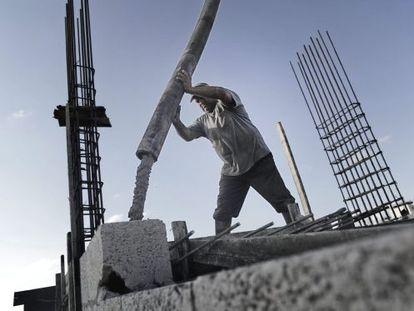 Um operário palestino derrama cimento no teto de um edifício.