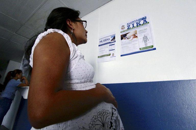 Mulher grávida lê anuncio sobre a Zika