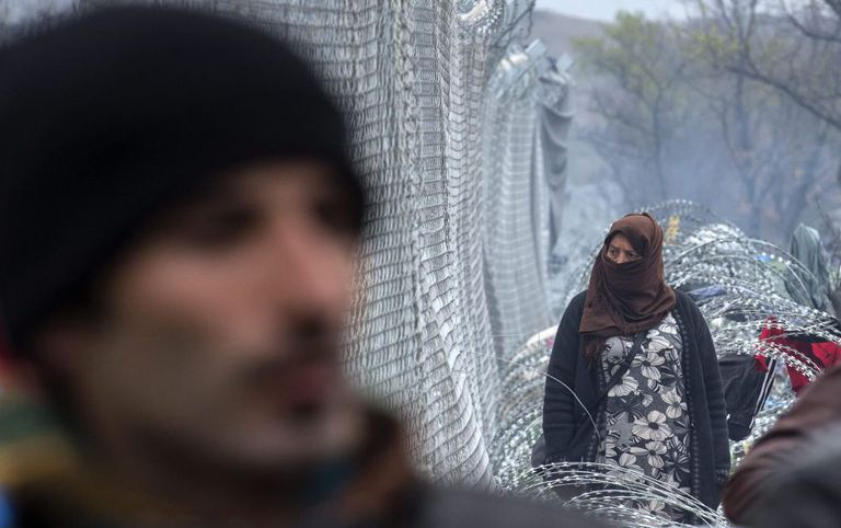 Mulher observa cerca que barra passagem de refugiados na região da Macedônia.