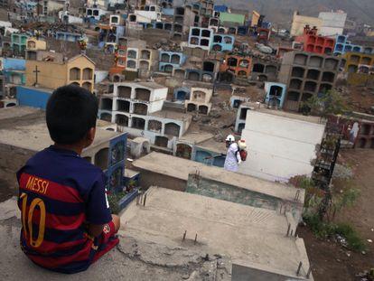 Criança com a camiseta de Messi observa um trabalhador que dedetiza o cemitério Mártires 19 de Julio, em Lima, no Peru, para evitar a proliferação do vírus do dengue, o chikungunya e Zika.