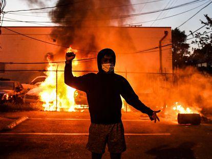 Manifestante ergue o punho diante de carros queimados, na quarta-feira, em Minneapólis.