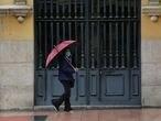 Una mujer pasa frente a una puerta en la capital en un día de lluvia y bajada de temperaturas en toda España, en que en gran parte de la Península y Baleares se espera nubosidad, con chubascos y tormentas casi generalizados, que podrán ser localmente fuertes o persistentes en zonas del nordeste peninsular, Galicia, oeste del sistema Central y Andalucía, en Madrid (España), a 14 de mayo de 2020. 14 MAYO 2020 LLUVIA;CORONAVIRUS;COVID-19;ESTADO DE ALARMA; Marta Fernández Jara / Europa Press 14/05/2020