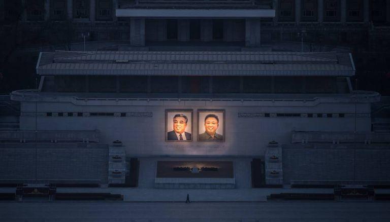 Homem passeia sob os dois grandes retratos de Kim Il-sung (esq.) e Kim Jong-il (dir.) em Pyongyang.