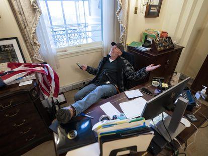 Seguidor de Trump sentado no escritório de Nancy Pelosi depois da invasão do Capitólio nesta quarta-feira.