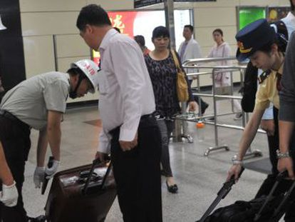 Seguranças revistam as bagagens dos passageiros na estação de trens de Guangzhou.