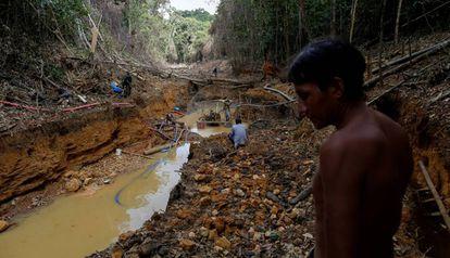 Indígena acompanhado de agentes da Funai durante uma operação contra o garimpo ilegal de ouro no território ianomâmi, em Roraima, numa imagem de arquivo.