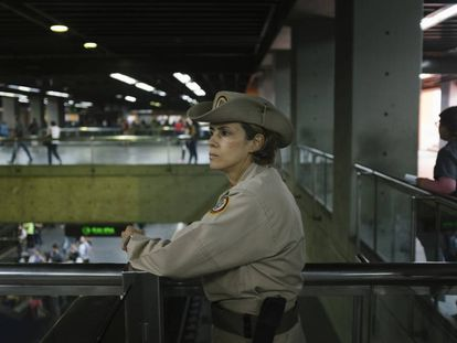 Carolina González, cabo da milícia, observa aos usuários do metro na estação Altamira, em Caracas.