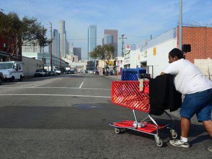 Uma mulher sem teto caminha pelas ruas do centro de Los Angeles.