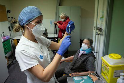 Uma enfermeira se prepara para injetar a primeira dose da vacina contra a covid-19 em uma idosa de Barcelona, em 3 de março.