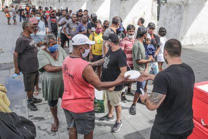 Voluntários distribuem comida a pessoas pobres no Rio de Janeiro, em abril.