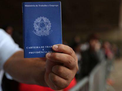 Um homem exibe sua carteira de trabalho enquanto aguarda na fila por emprego em São Paulo.