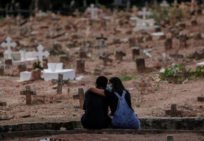 Casal chora a morte de uma mulher vítima de covid-19 sepultada em cemitério do Rio de Janeiro na terça-feira.