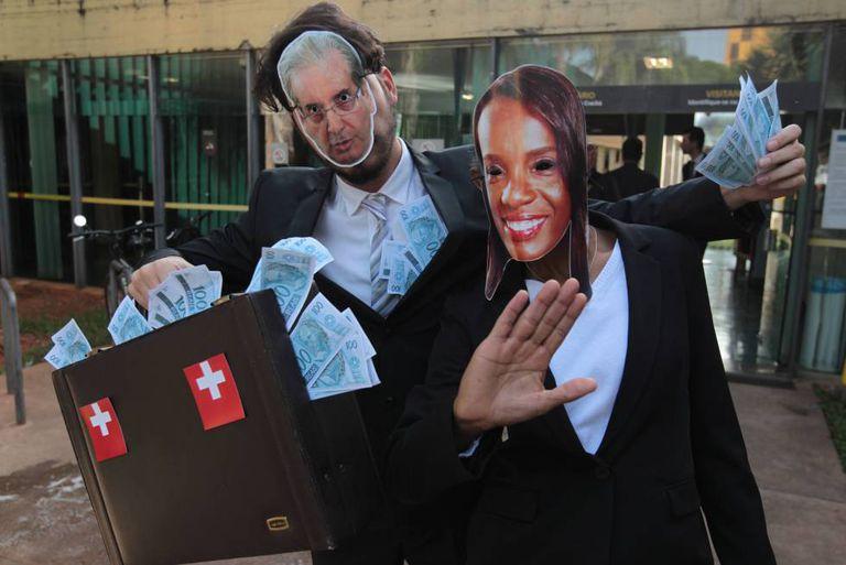 Manifestantes com máscaras de Eduardo Cunha e Tia Eron em frente à Câmara.