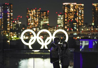 Casal faz selfie diante dos anéis olímpicos em Tóquio.