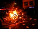 A demonstrator rides a bike at a barricade set on fire during clashes with riot police which erupted during a protest against the death of a lawyer under police custody, in Bogota, early on September 10, 2020. - A man who was detained by police officers died Wednesday in Bogota after receiving repeated electric shocks on the ground with a stun gun. (Photo by STR / AFP)
