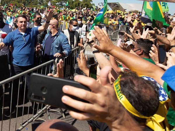 """-FOTODELDÍA- AME3398. BRASILIA (BRASIL), 31/05/2020.- El presidente brasileño, Jair Bolsonaro, saluda este domingo a sus simpatizantes durante una manifestación en Brasilia (Brasil). Bolsonaro volvió a ignorar este domingo la gravedad del COVID-19, que deja ya casi 30.000 muertes en el país, y asistió a una manifestación en la que hasta se paseó montado a caballo ante miles de personas. El acto se desarrolló a las puertas del Palacio presidencial de Planalto, y como ha ocurrido en manifestaciones que el """"bolsonarismo"""" celebró los últimos domingos, hubo protestas contra el Congreso y la Corte Suprema, que según los partidarios del líder de la ultraderecha """"conspiran"""" contra el Gobierno. EFE/ Joédson Alves"""