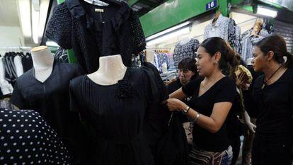 Cidadãs tailandesas em busca de roupa negra para o luto pela morte do rei Bhumibol.