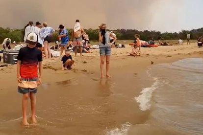 Um grupo de pessoas se refugia dos incêndios na terça-feira em Batemas Bay (Austrália).