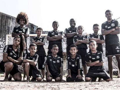 Maria Dias, Edu e Taílson com crianças de comunidade em Praia Grande na campanha de lançamento do terceiro uniforme.
