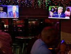 The dual town halls of U.S. Democratic presidential candidate Joe Biden and U.S. President Donald Trump, who are both running in the 2020 U.S. presidential election, are seen on television monitors at Luv Child restaurant ahead of the election in Tampa, Florida, U.S. October 15, 2020.  REUTERS/Octavio Jones