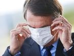 Brazil's President Jair Bolsonaro adjusts his mask as he leaves Alvorada Palace, amid the coronavirus disease (COVID-19) outbreak in Brasilia, Brazil May 13, 2020. REUTERS/Adriano Machado