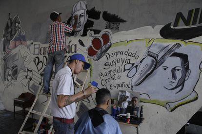 Gilbert Arteaga atende na sexta-feira um cliente em sua barbearia improvisada sob uma ponte em Caracas.