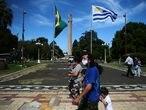 People walk on the International Square, amid the coronavirus disease (COVID-19) pandemic, at the border of Brazilian city Santana do Livramento and Uruguayan city of Rivera, Uruguay March 19, 2021. Picture taken March 19, 2021. REUTERS/Diego Vara