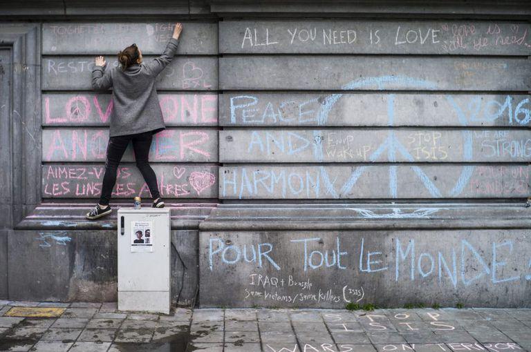Uma jovem escreve, nesta quarta-feira, mensagem em muro da Praça da Bolsa de Bruxelas em homenagem às vítimas dos atentados terroristas.