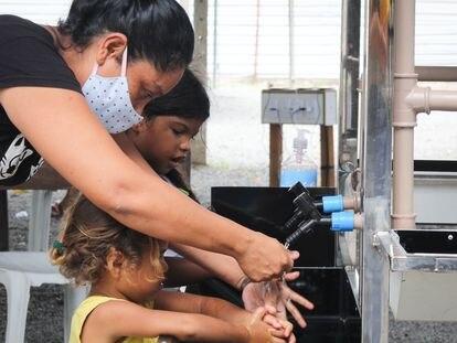 Crianças lavam as mãos em Roraima, no norte de Brasil.