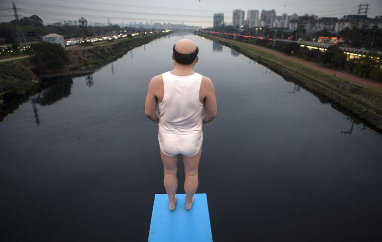 """Batizada de """"As Margens do Rio Pinheiros"""", uma intervenção do artista plástico de Eduardo Srur alerta para a poluição dos rios de São Paulo. Na imagem, uma estátua de um homem ameaça saltar de um trampolim em um dos rios mais contaminados do Brasil."""