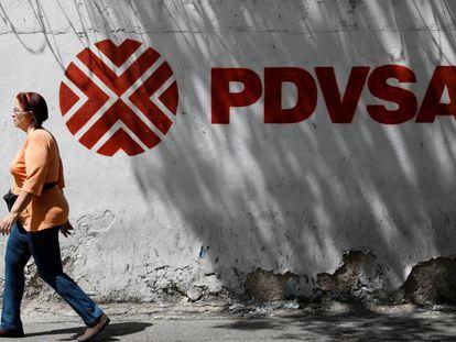 Uma mulher caminha em frente ao logotipo da petroleira venezuelana PDVSA em Caracas.