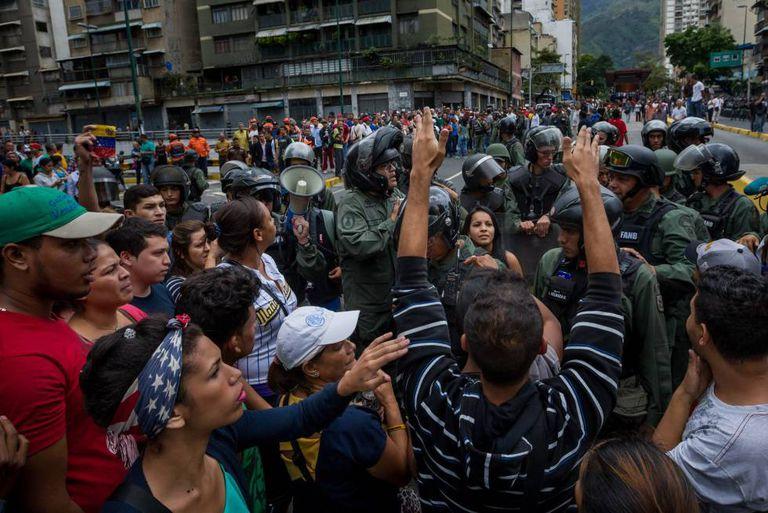 Manifestantes enfrentam membros da Guarda Nacional Bolivariana, em Caracas, em protesto contra a falta de alimentos.