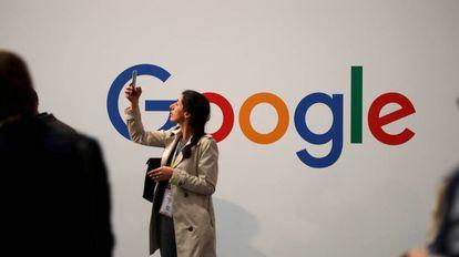 – Usuária consulta seu celular ao lado do logo do Google.