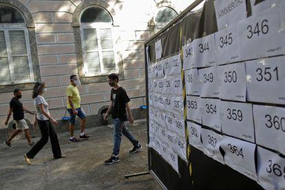Eleitores passam por cartazes com números de seções de votação na região do Flamengo, no Rio, no último domingo.