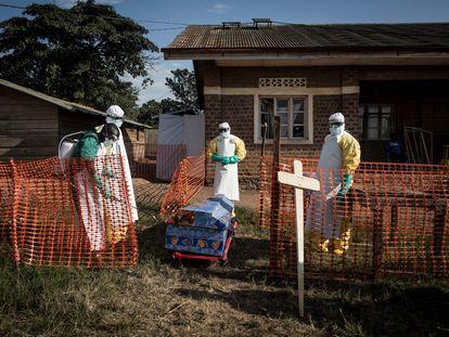 Agentes sanitários desinfetam um caixão durante enterro seguro em agosto de 2018 na localidade de Beni, nordeste do Congo.