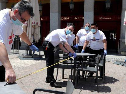 Funcionários montam e fazem a limpeza de mesas de um restaurante no centro de Madri.