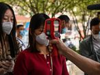 A worker wearing a face mask checks passengers body temperatures and a health code on their phones before they take a taxi after arriving at Hankou railway station in Wuhan, Hubei Province on May 12, 2020. - China reported no new domestic coronavirus infections on May 12, after two consecutive days of double-digit increases, including a new cluster over the weekend in Wuhan, which fuelled fears of a second wave of infections. (Photo by Hector RETAMAL / AFP)