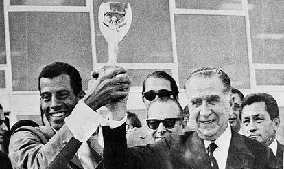 Carlos Alberto levanta a taça de campeão com o ditador Emílio Médici.