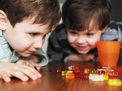 Duas crianças olhando ansiosas para doces.