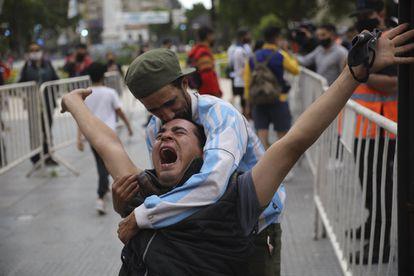 Homens se abraçam em Buenos Aires para se consolar pela morte de Diego Maradona.
