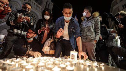 Pessoas acendem velas do lado de fora da Basílica de Notre-Dame de l'Assomption, em Nice, em homenagem às três vítimas do atentado.