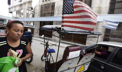 Táxi puxado por bicicleta exibe bandeiras dos EUA e de Cuba em Havana.