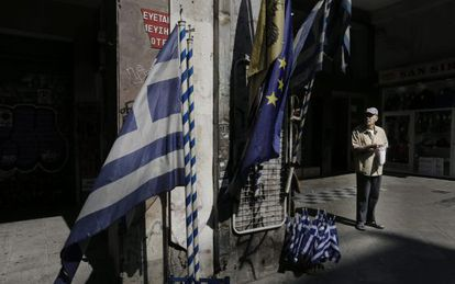 Um idoso em frente a uma loja que vende bandeiras gregas e da UE no centro de Atenas.
