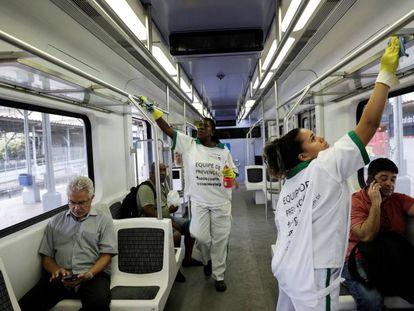 Duas mulheres desinfectam o metrô do Rio de Janeiro.