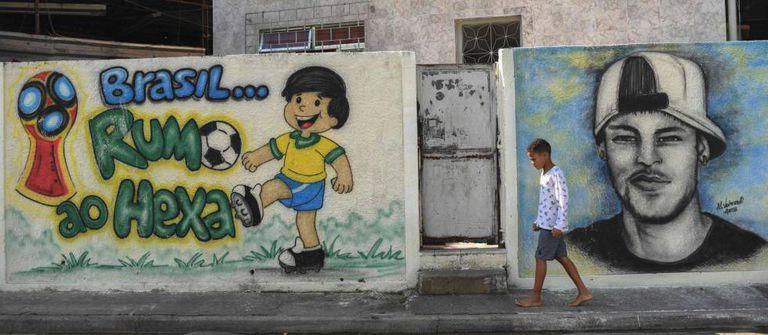 Menino caminha diante de grafites sobre a Copa no Rio.
